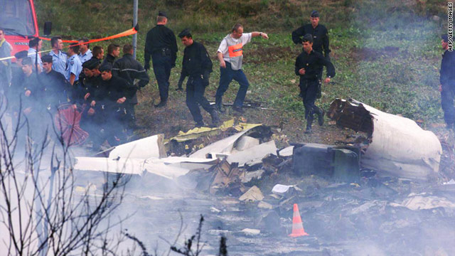 Policemen stand among the debris of the Concorde that crashed near Paris on July 25, 2000.