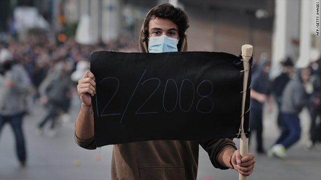 """A youth in Athens holds up a black flag reading """"12/2008,"""" the date of the death of teenager Alexis Grigoropoulos."""