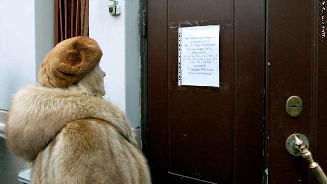 A woman reads a notice pinned to the court door announcing the postponement of Mikhail Khodorkovsky's corruption trial.