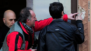 Spanish forensic experts investigate a bullet hole the scene in Barcelona on Wednesday.