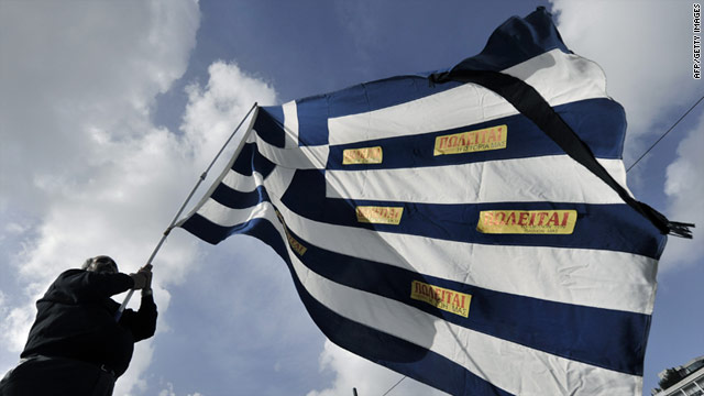 """For sale"" notices are on a Greek flag waved by a demonstrator outside the Greek parliament in Athens on Wednesday."