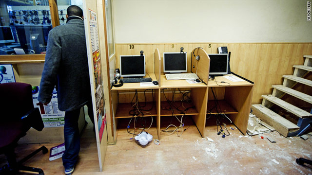 A Rotterdam pawn shop and internet cafe was searched by police investigating 12 men suspected of planning violent attacks.