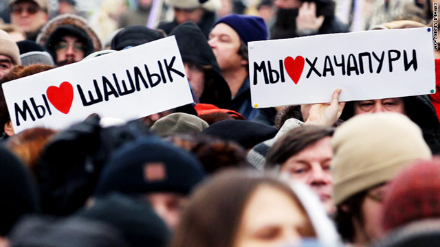 People hold posters reading 'We like kebab!' and 'We like khachapuri!' (Georgian cheese pastry) during a rally in Moscow.