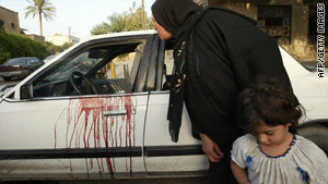 A woman peeks inside a blood-stained car in Baghdad, Iraq, after the shootout in 2007.