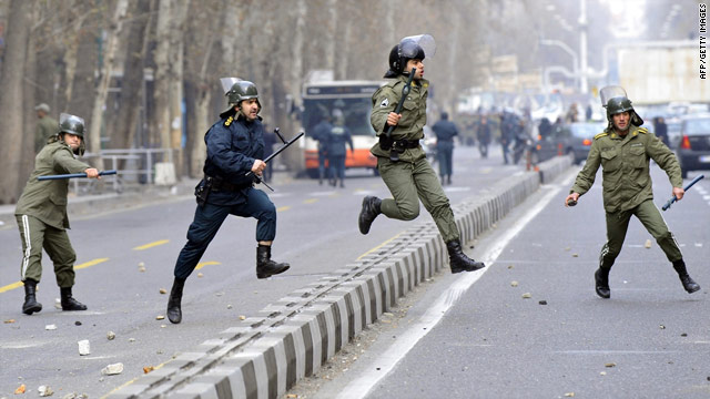 Iranian riot policemen pursue opposition supporters during protests in Tehran on December 27, 2009.