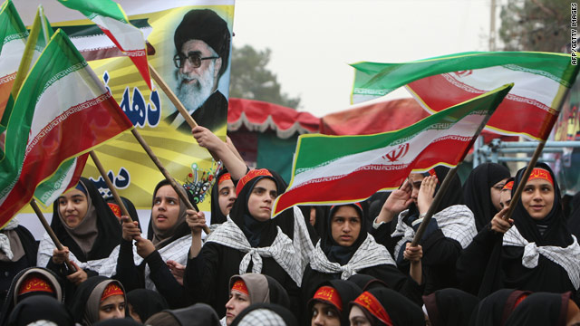 Schoolgirls wave Iranian flags as they mark the start of 10 days of celebrations for the anniversary of the Islamic revolution at the Behesht-e Zahra (Zahra's Paradise) cemetery in southern Tehran on February 1, 2010.