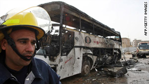 An Iraqi firefighter walks past the wreckage of a bus at the site of a blast in the holy city of Najaf.
