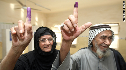 Iraqis holding up their ink-stained index fingers to show they have voted.