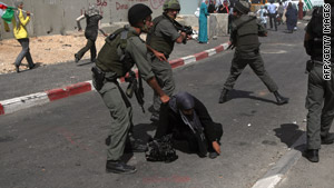 A woman falls to the ground as Israeli soldiers detain her Saturday during a protest at the Qalandia checkpoint.