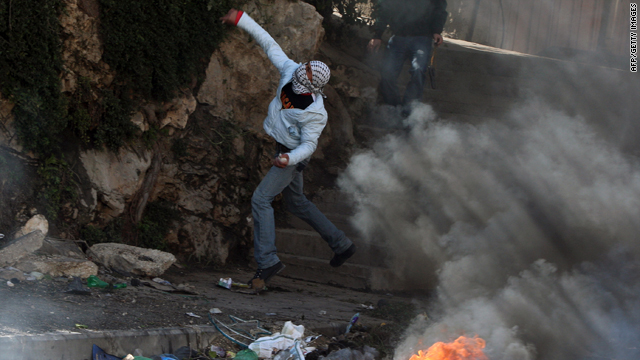 A Palestinian youth hurls stones at Israeli soldiers during clashes in the West Bank refugee camp of Qalandia on Thursday. Tensions over an Israeli announcement of new settlement plans have helped spark the worst riots in years.