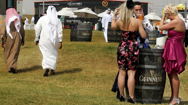 Emirati men walk past foreigners drinking beer at the 2009 Horse Racing Dubai World Cup. Some 85 percent of Dubai's population are foreigners.