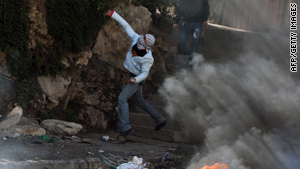 A Palestinian youth hurls stones at Israeli soldiers at the West Bank refugee camp of Qalandia on Thursday.