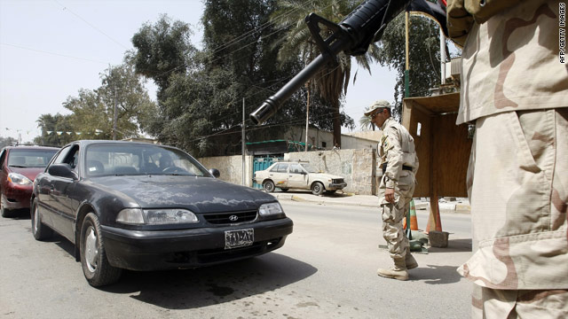 Iraqi soldiers stop vehicles Saturday at a checkpoint in Baghad after an attack near the capital killed 25 people late Friday.
