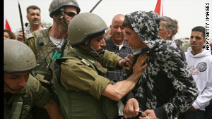 Israeli soldiers detain a demonstrator during a protest along the West Bank barrier on Sunday.