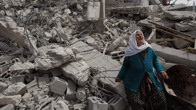 A Palestinian woman stands in front of her West Bank house on April 14 after its demolition by Israeli army bulldozers.