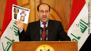 Iraqi Prime Minister Nuri al-Maliki displays a photo of the body of Abu Omar al-Baghdadi.
