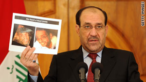 Iraq's Prime Minister Nouri al-Maliki holds images of man identified as Abu Ayyub al-Masri on April 19.
