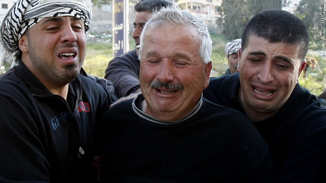 The father of a Palestinian teen and other family members mourn his death in the West Bank on March 20.