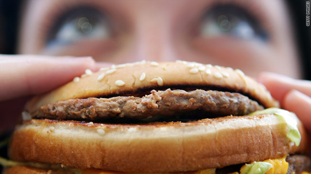 A woman bites into a burger. Kuwait's enthusiasm for fast food is contributing to its obesity problem.