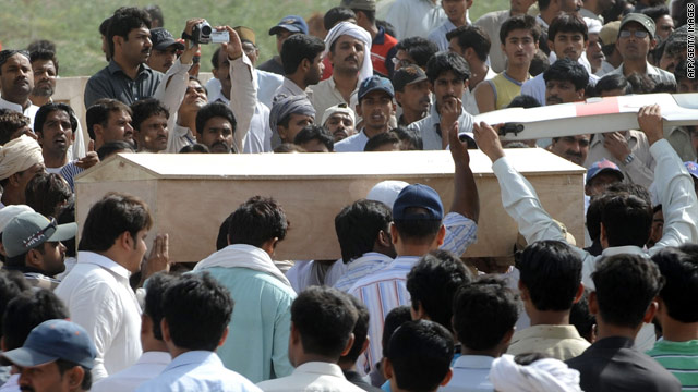 Pakistani Ahmadi community members carry a coffin of a victim during a funeral ceremony on May 29.