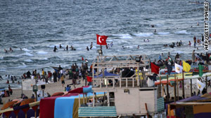 Palestinians gather on the beach in Gaza City about a week after an Israeli attack on a Gaza-bound aid flotilla.