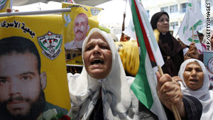 Women in Gaza hold pictures of Palestinian men held in Israeli jails during a protest in Gaza on Sunday.