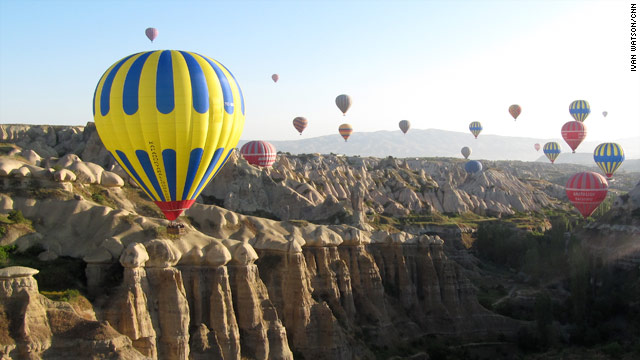 Hot air balloons float over the otherworldly landscape of Cappadocia, Turkey.