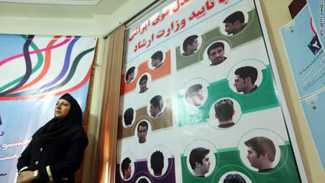 A woman in Tehran on Monday stands next to a board with pictures of men's hairstyles authorized by Iran.