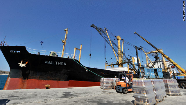 Workers load supplies on to a cargo ship at the Lavrio port, southeast of Athens, Greece, on Friday.