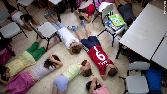 School children in Tel Aviv take cover during a nationwide drill in May to prepare the public for an emergency situation.