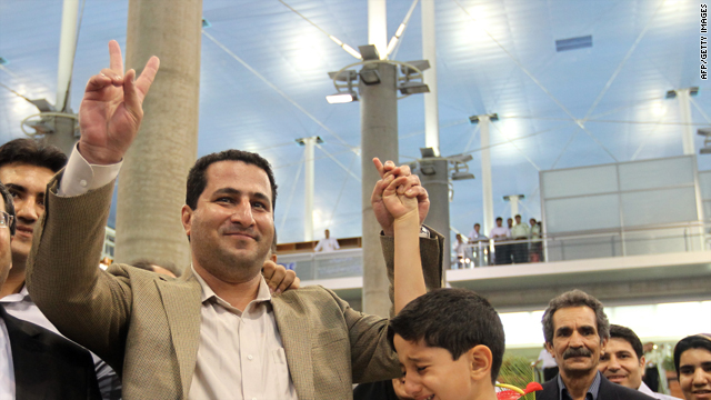 Iranian nuclear scientist Shahram Amiri holds his weeping son's hand as he flashes the victory sign upon arrival at Imam Khomeini Airport in Tehran on July 15, 2010.