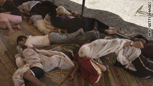 Bedouin women and children sleep in the shade after being escorted from their village.