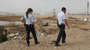 Israeli police inspect the site where a rocket reportedly landed on the outskirts of Eilat.