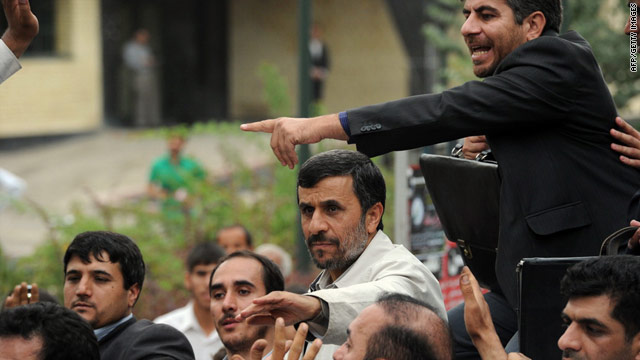 Bodyguards surround Iranian President Mahmoud Ahmadinejad (c) as they react to the incident in the city of Hamedan.