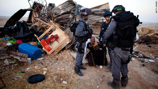 Israeli policemen surround a Bedouin woman as she sits next to her wrecked house in the Al-Akarib village, August 10, 2010.