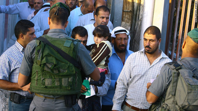 Palestinian Muslims show their IDs at an Israeli army checkpoint in the West Bank city of Bethlehem on August 13, 2010.