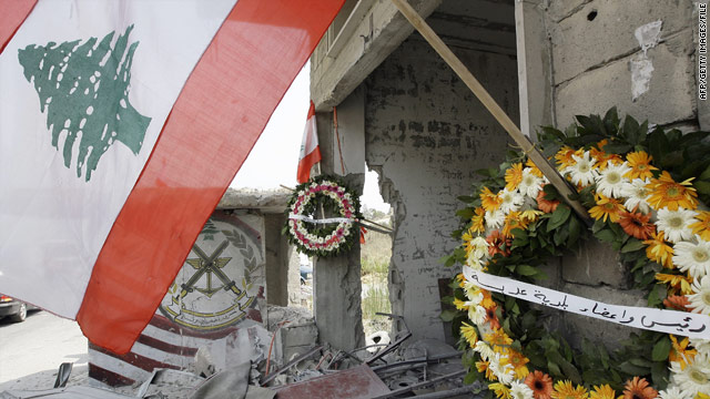 A Lebanese flag and wreaths at the spot where two Lebanese soldiers died in a firefight over tree cutting.