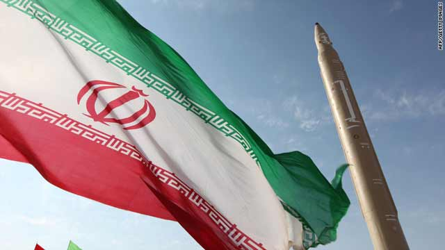 An Iranian flag flutters Friday at an undisclosed location in Iran next to a surface-to-surface Qiam-1 (Rising) missile.