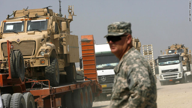 A U.S. soldier watches as military vehicles that had been in Iraq are moved to an undisclosed base in Kuwait.