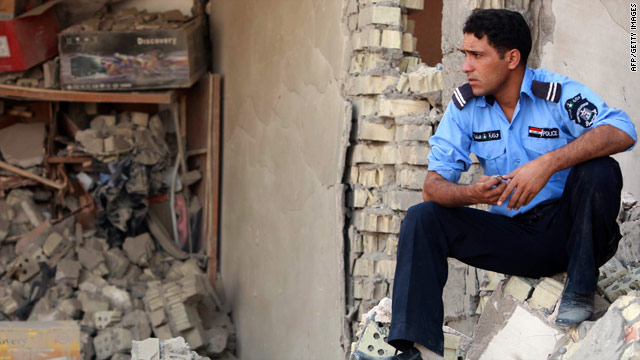 A police officer surveys rubble in Karbala, south of Baghdad. Militants launched a wave of  bombings Wednesday across Iraq.