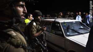 Israeli soldiers inspect a settlers' car after it was ambushed by Palestinian gunmen in the southern West Bank Tuesday.
