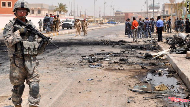 Iraqi soldiers and policemen stand at the site of a suicide car bomb attack in in northeastern Baghdad  on August 25.