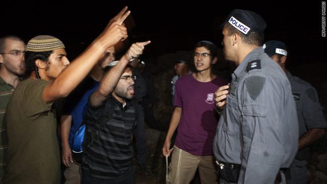 Israeli settlers express anger in front of Israeli policemen after a settler's car was ambushed by gunmen.