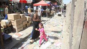 A mother and child run Sunday after a suicide bombing at Iraqi military headquarters in central Baghdad.