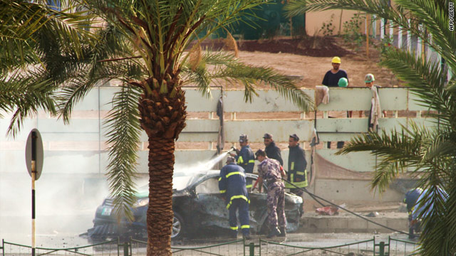 Police douse a fire after a rocket smashed into a street in the Jordanian port city of Aqaba on August 2, 2010.