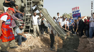 Israeli settlers surround a cement mixer as it pours cement into a new house in a West Bank settlement on Sunday.