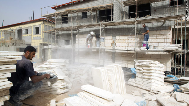 Workers build new housing on Sunday in Ariel, an Israeli settlement on the West Bank.