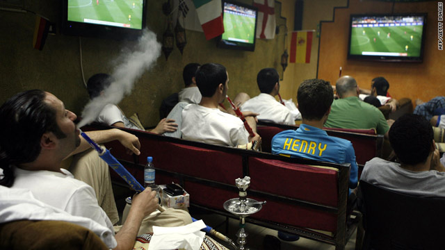 Arab men smoke waterpipes as they watch a World Cup match at a coffee shop in Kuwait in June.
