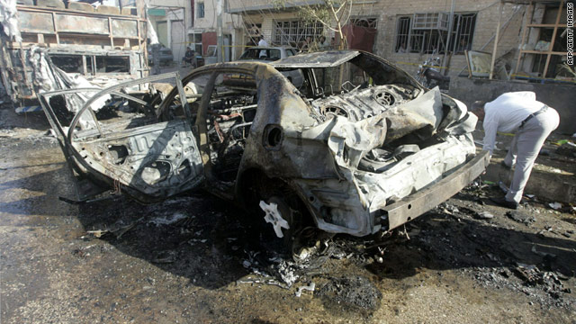 A man checks out the charred remains of a vehicle targeted in a bombing Monday in Najaf, Iraq.