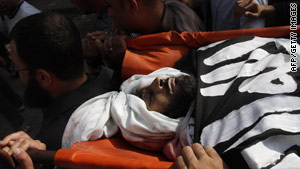 Palestinian mourners carry the body of Islam Yassin during his funeral iin Gaza on November 18.